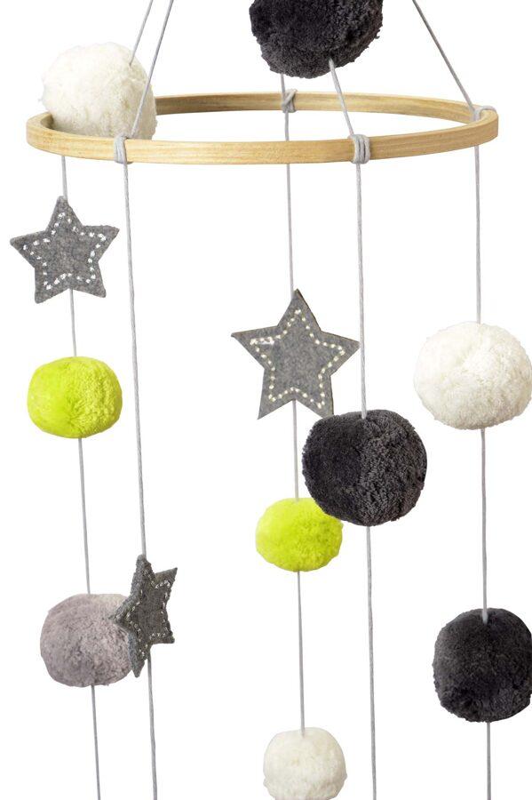 Zīdaiņu gultiņas dekors ar pompomiem un zvaigznītēm